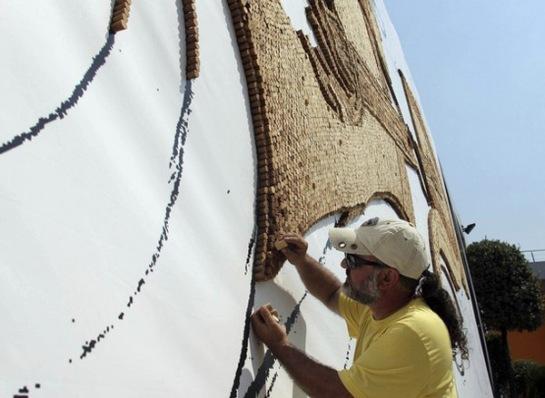 Albanian artist Strati creates a cork mosaic of a guitarist at the Sheraton Hotel in Tirana